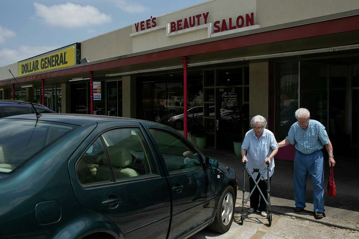 Jerome Weynand, 92, walks with his wife, Adrienne Weynand, 91, to their car after Adrienne had her hair done at Vee's Hair and Spa. Adrienne has been a Vee's customer for more than 50 years.