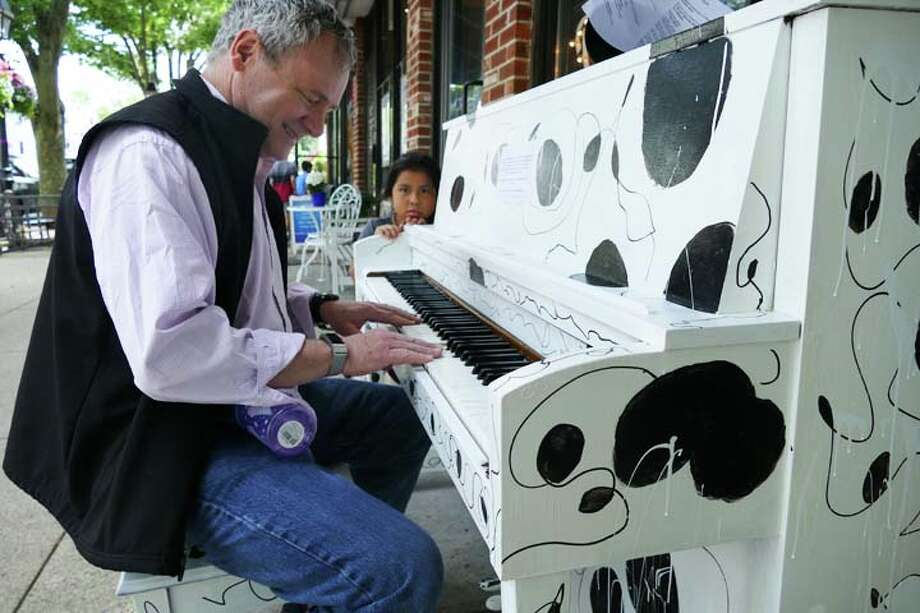Chris Conroy plays the piano for his daughter, Anna, outside of Kafo on Main Street during Make Music Day, June 21. — Steve Coulter photo