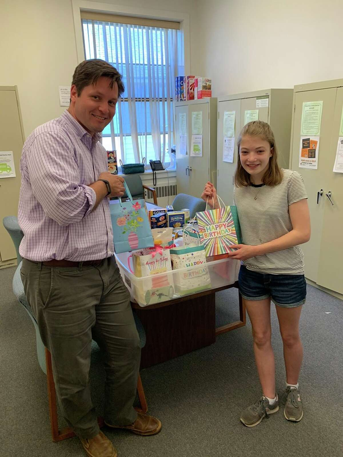"""Devon Noonan, who graduated from East Ridge Middle School in June, stands with Social Services Director Tony Phillips inside the food pantry at town hall. Before her graduation, Devon dropped off a whole bin of """"Birthday Bags."""" She and other students and teachers collected birthday bag items for food pantry consumers."""