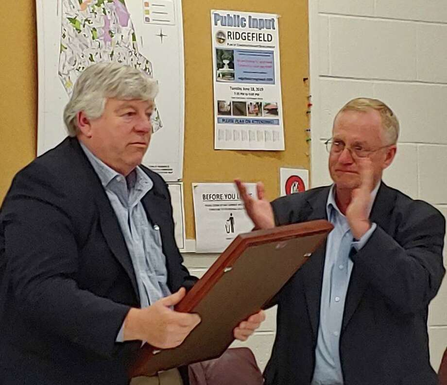 Lifelong Ridgefielder Charlie Knoche, left, received a plaque from the Police Commission Chairman George Kain in recognition for his 24 years of service on the commission. He stepped down June 13.