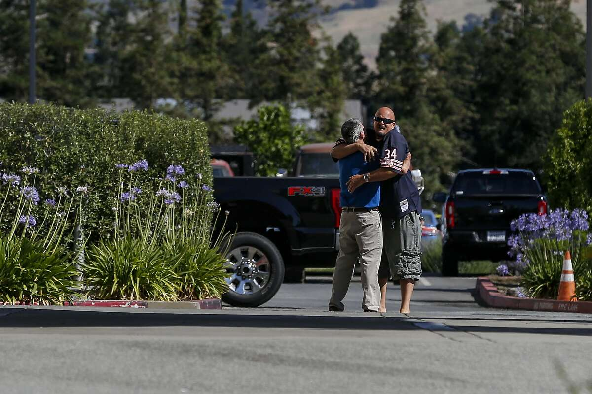Two men embrace in the parking lot of the Morgan Hill Ford dealership on June 26, 2019. The night before night police were called to the dealership where a man reportedly killed two people before turning the gun on himself.