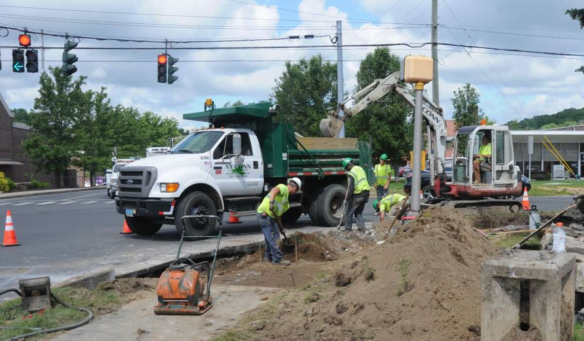 Workers from the contracting firm NYCONN dig at the corner of Farmingville Road and Route 35, putting in a new traffic light system.