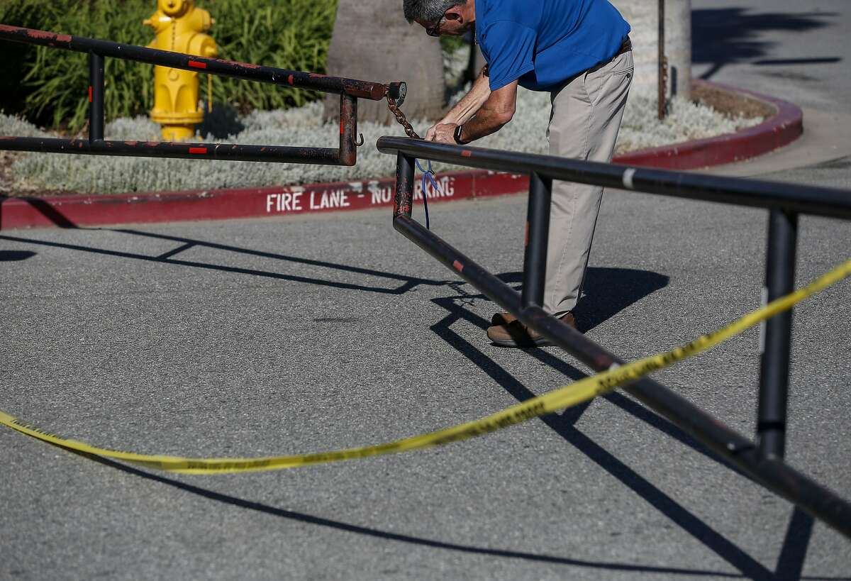 An employee tries to unlock a gate strewn with police tape at the Morgan Hill Ford dealership Wednesday, June 26, 2019, in Morgan Hill, Calif. The night before night police were called to the dealership where a man reportedly killed two people before turning the gun on himself.