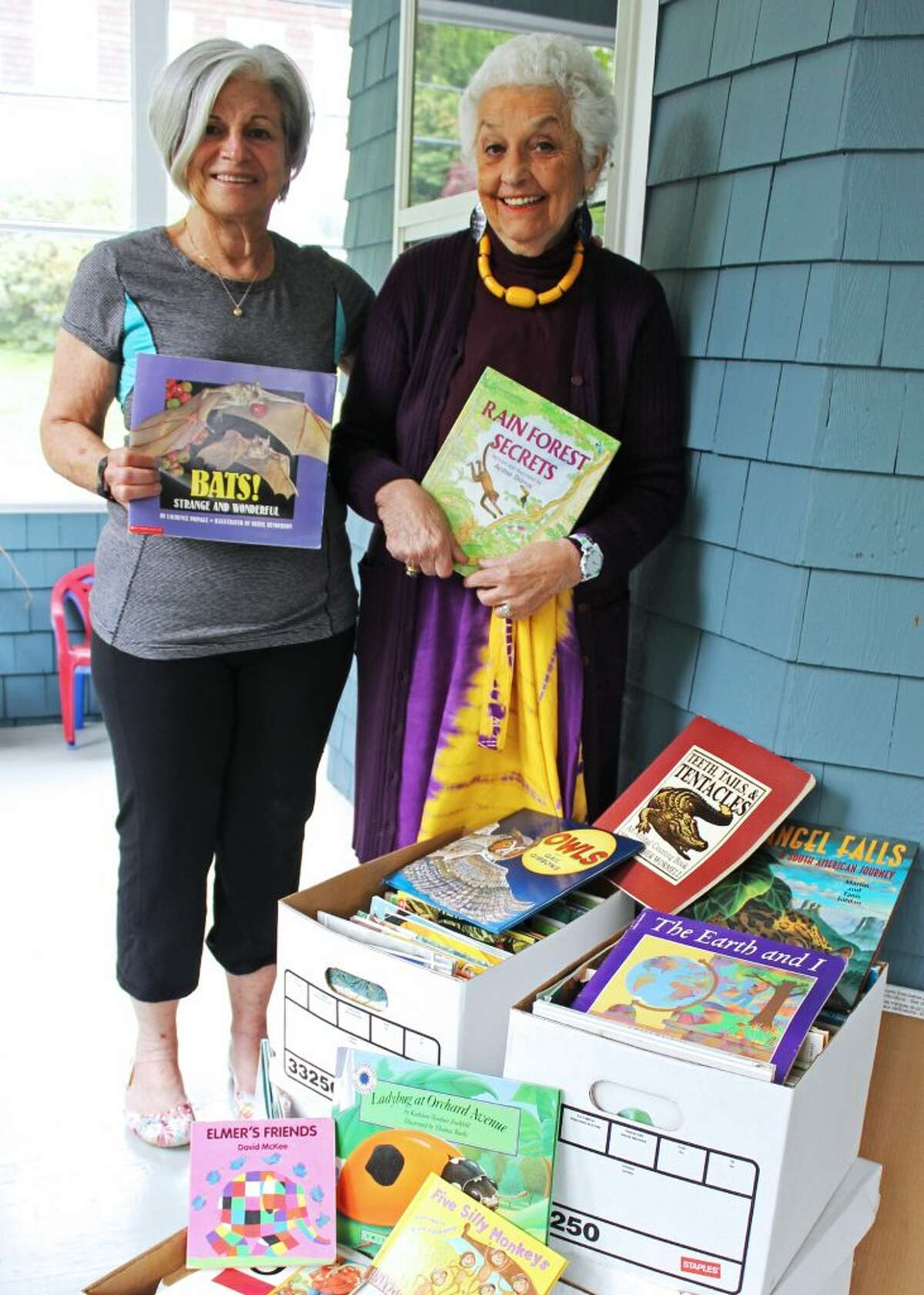 Professor Emerita of Social Work Dr. Patti Ivry and Professor Emerita of Education Dr. Darla Shaw with some of the books Shaw donated to the Impact Network to promote literacy in Zambia.