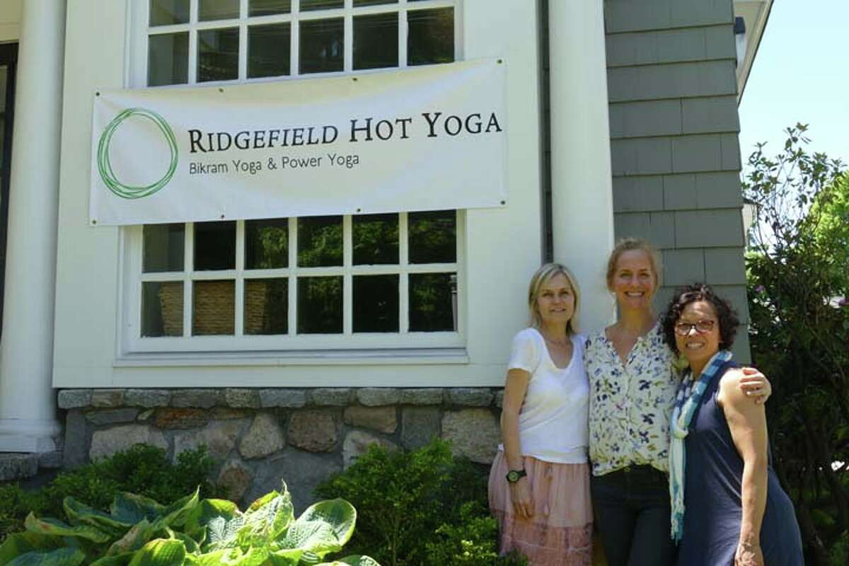 The Ridgefield Hot Yoga team, from left: Wendy Boscia, Leah Bey-Wagner and Maritza Johnson in front of the studio's new sign.