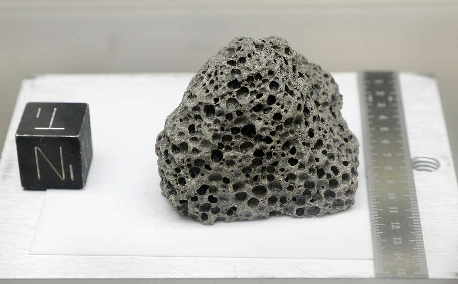 Collected during Apollo 15, a 3.5 billion years old basalt rock is displayed in a pressurized nitrogen-filled examination case at the NASA Johnson Space Center in Houston. Photo: Michael Wyke / Associated Press