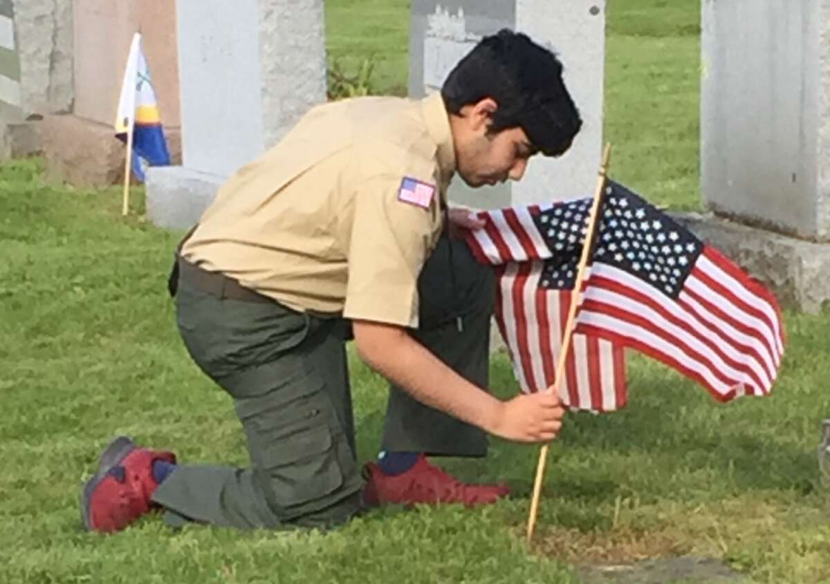 Vivek Bagal, a Ridgefield High School student and a scout with Troop 76, honored those who served in the military by placing American flags at the tombstones of veterans in Mapleshade Cemetery Friday, May 24.