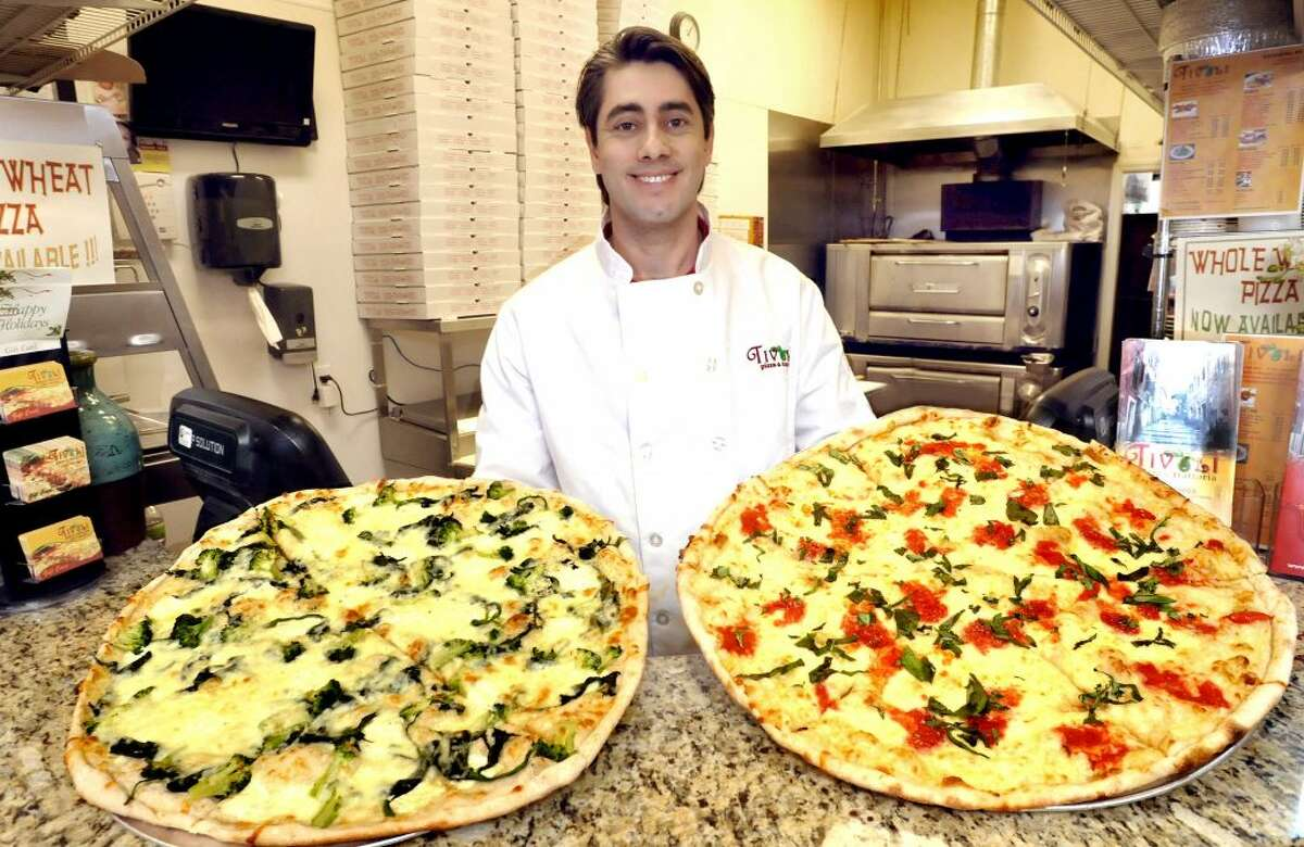 Junio Filgueira, owner of Tivoli Pizza in Danbury, holds a spinach pizza, left, and authentic margarita pizza. He will have a restaurant opening in Ridgefield later this year and a mobile pizza truck.