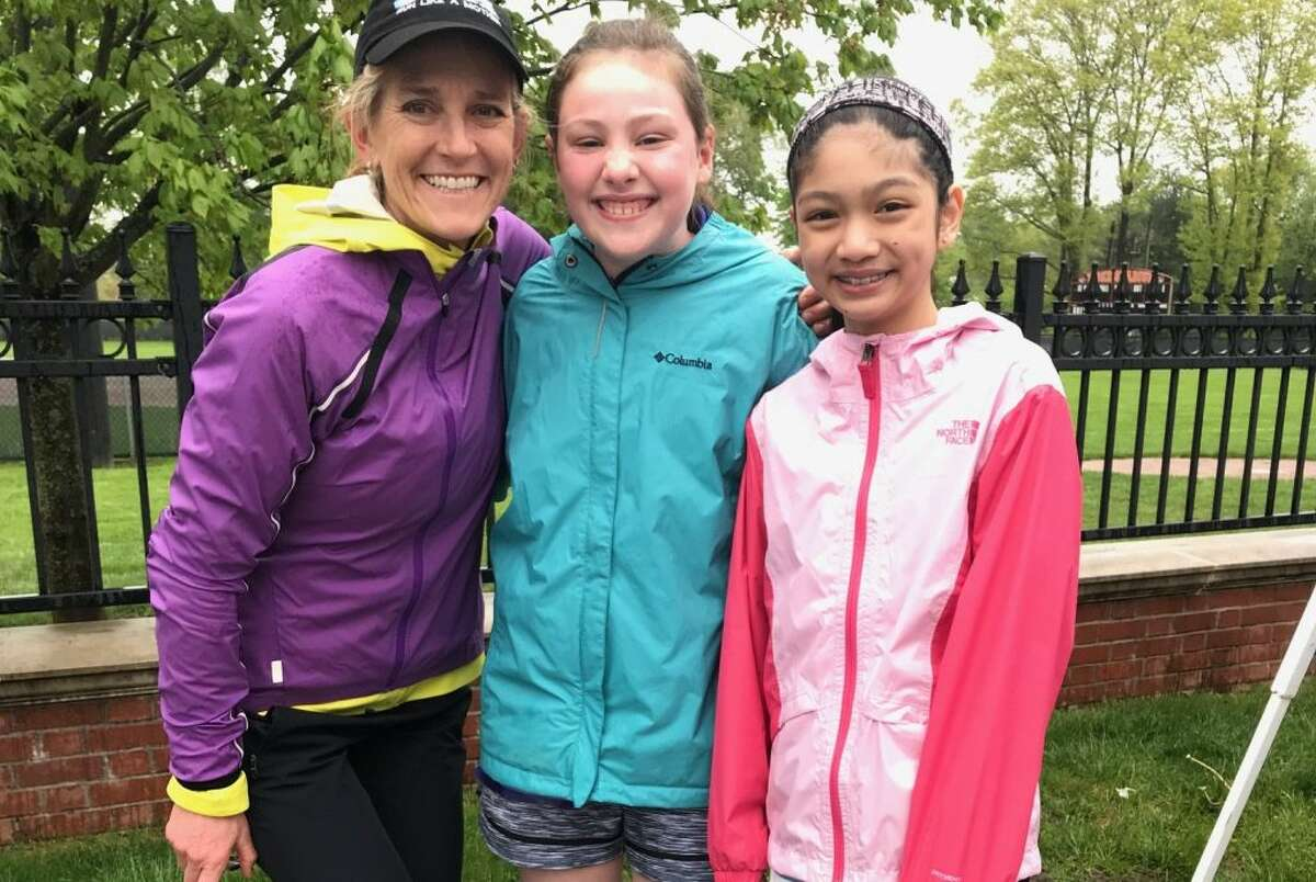 Kyela McGuire and Juliette Arencibia of Ms President US posed for a picture with Megan Searfoss after the annual Run Like a Mother 5K on May 12. Searfoss, owner of Ridgefield Running Company, founded the race.