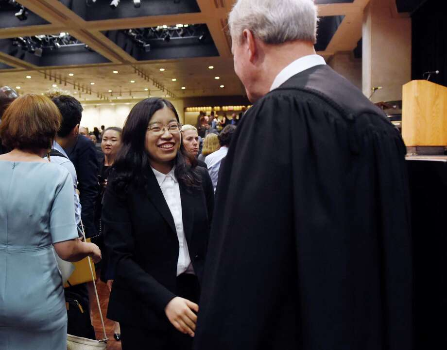 Tianran Xu of China shakes hands with Judge Phillip R. Rumsey after a ceremony to admit new members into the New York State Bar on Wednesday, June 26, 2019 at the Empire State Plaza Convention Center in Albany, NY. (Phoebe Sheehan/Times Union) Photo: Phoebe Sheehan, Albany Times Union / 20047308A