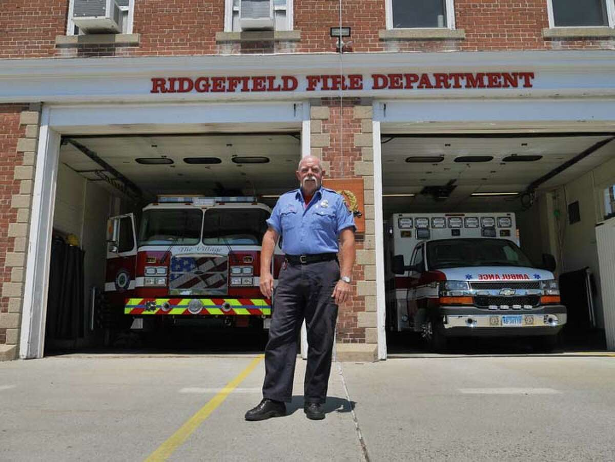 Retired fire Lt. Brian Jones stands in front of the fire engines outside of Ridgefield fire headquarters on Catoonah Street. - Steve Coulter photo