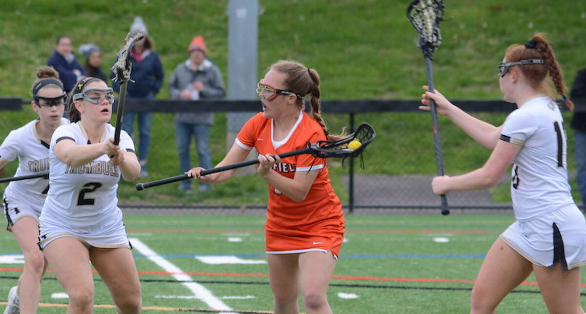 Maddie McGrath draws a crowd of Trumbull players during Thursday's girls lacrosse game. - Andy Hutchison photo