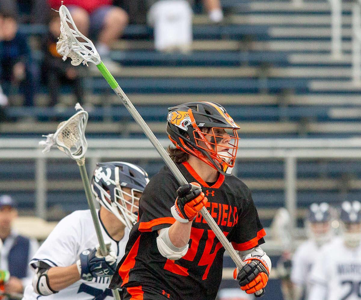 Kai Prohaska looks to make a pass during Ridgefield's win over Wilton. - GretchenMcMahonPhotography.com
