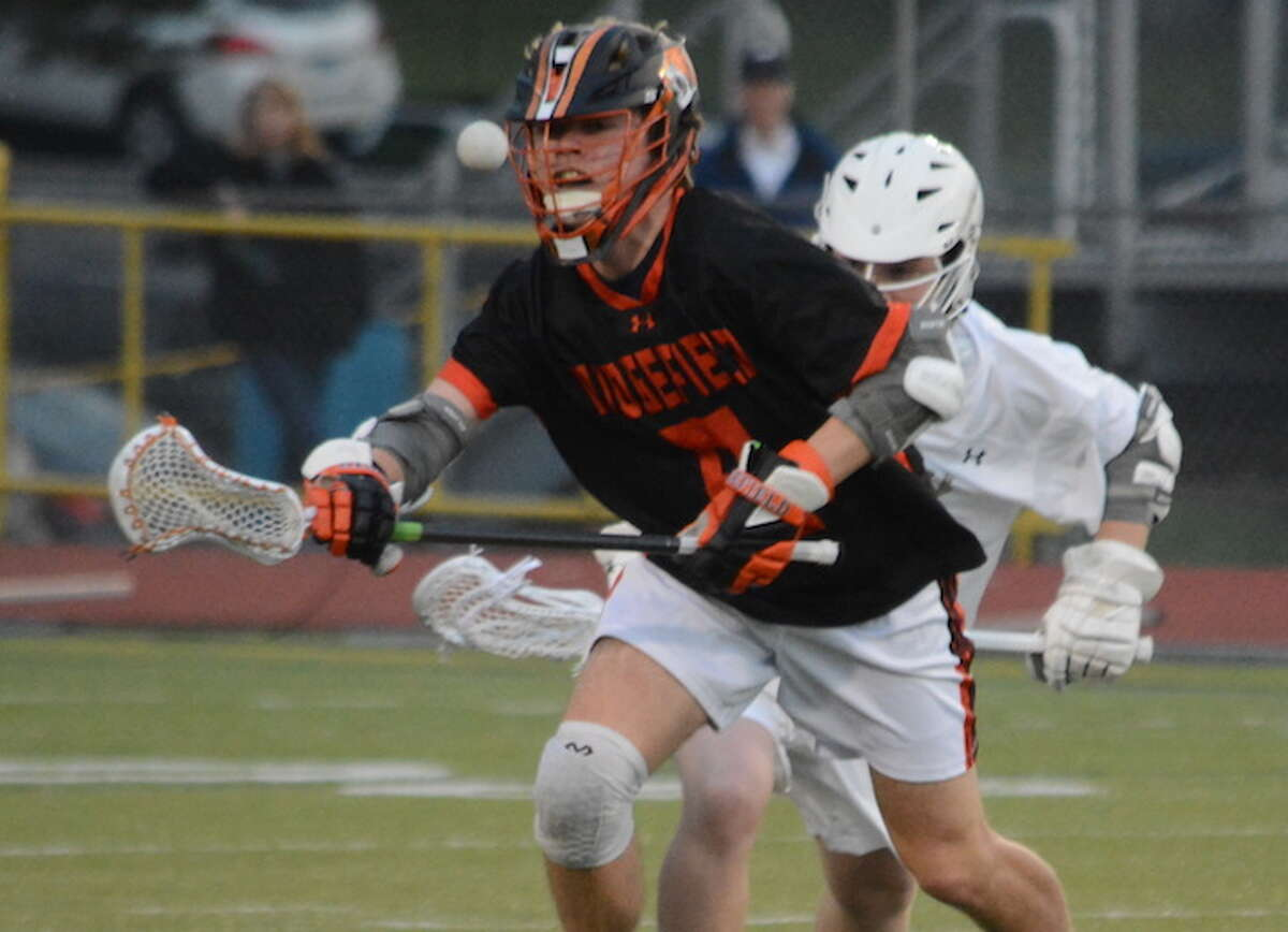 Jake Lynne controls a face-off during Ridgefield's 16-6 win over Trumbull. - Andy Hutchison photo