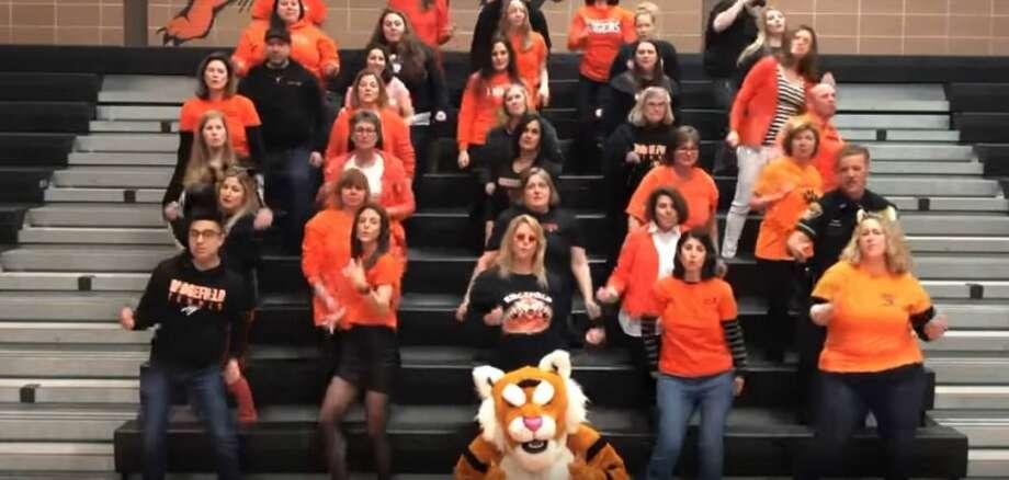 Ridgefield High School teachers dance in the school's gym.