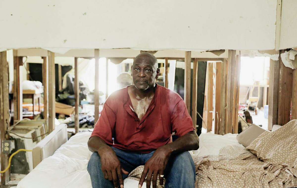 Joe Fowler sits in a bed he sometimes naps on with his son in his Kashmere Gardens home on Tuesday, June 18, 2019 in Houston. The home took in three feet of water and Fowler is still in the process of trying to secure funds. Fowler grew up in the five-bedroom home, but a Texas General Land Office rule would limit his rebuild to two bedrooms.