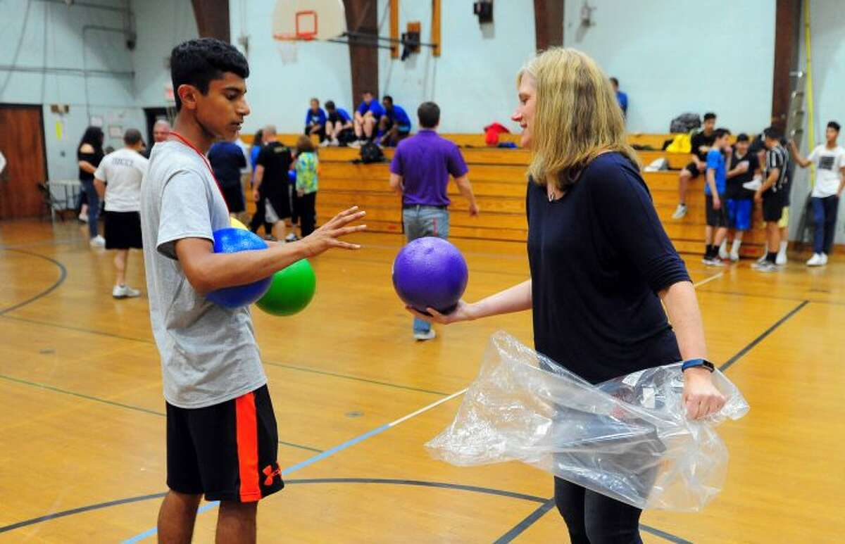 Melissa McGarry hands out dodgeballs to players taking part in TPAUD's Dodge-a-Cop Dodgeball Tournament at Hillcrest Middle School. -Hearst CT Media