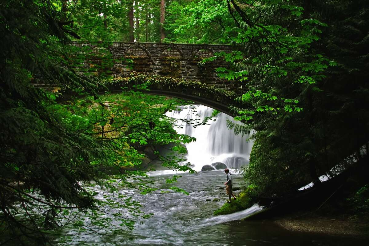 """After nabbing a beloved Boomer's hamburger, we'd suggest heading to Whatcom Falls and Whirlpool Falls. A native word meaning """"noisy water,""""Whatcomis the perfect name for Bellingham's most well-known waterfall. A 241-acre park in Bellingham, the falls are on Whatcom Creek, which leads from Lake Whatcom to Bellingham Bay. The park has four sets of waterfalls and several miles of well-maintained walking trails, alongside a fishing pond for teaching kids 14 and under how to bait their hooks and cast a line. New trail maps installed in 2019 make it easy to find your way among the trails and trees, and you can find Whirlpool Falls for soaking just north of the Waterline Bridge."""