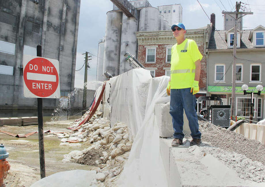 Alton Public Works employee Lloyd Roberts stands on top of the flood wall at the intersection of State and Broadway early Wednesday afternoon while waiting for a front-end loader to remove a concrete sections. Workers have begun the final process of removing the wall and cleaning and repairing the intersection, which should take about a week.