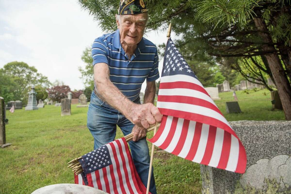 Air Force veteran Bing Ventres places a flag at the grave of a veteran at Hillside Cemetery.