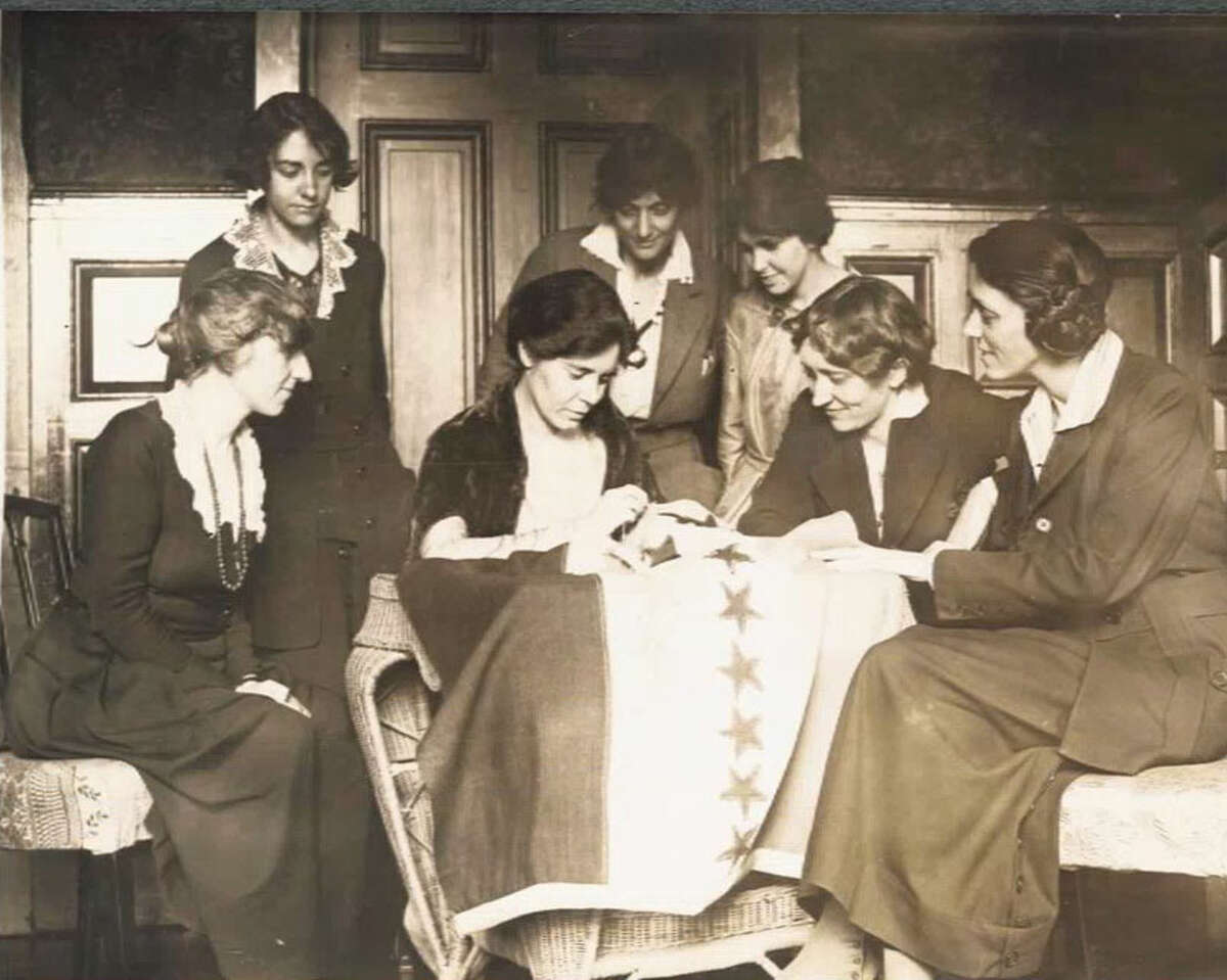 National Woman's Party activists watch Alice Paul of Ridgefield sew a star onto the NWP Ratification Flag, representing another state's ratification of the 19th Amendment. Contributed photo