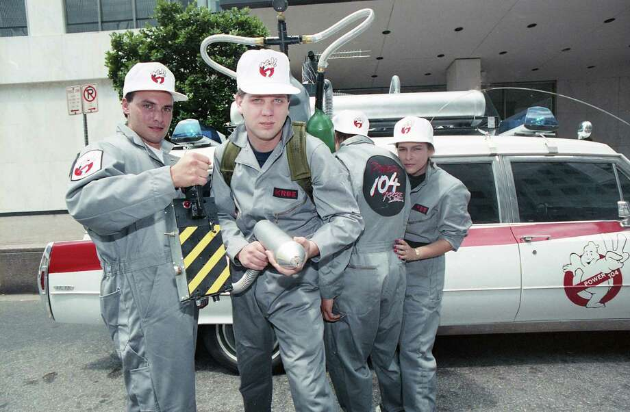 "KRBE DJs, including Glenn Beck, center, dressed as the Ghostbusters as part of a promotion to give away an Ecto-1 similar to the vehicle used in the ""Ghostbusters"" film. Here, the vehicle is parked outside the Houston Chronicle building at 801 Texas on June 8, 1989. The promotion is in advance of the release of ""Ghostbusters II."" Photo: Howard Castleberry, Houston Chronicle"
