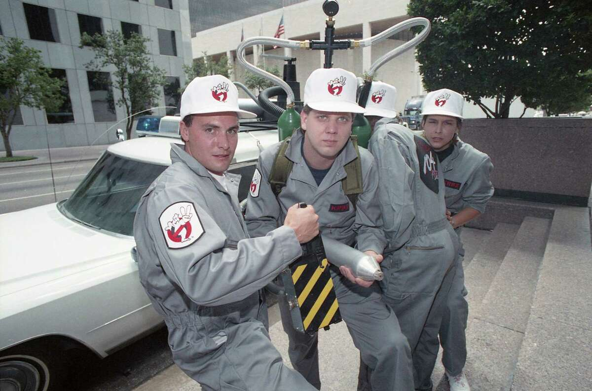 """KRBE DJs, including Glenn Beck, center, dressed as the Ghostbusters as part of a promotion to give away an Ecto-1 similar to the vehicle used in the """"Ghostbusters"""" film. Here, the vehicle is parked outside the Houston Chronicle building at 801 Texas on June 8, 1989. The promotion is in advance of the release of """"Ghostbusters II."""""""