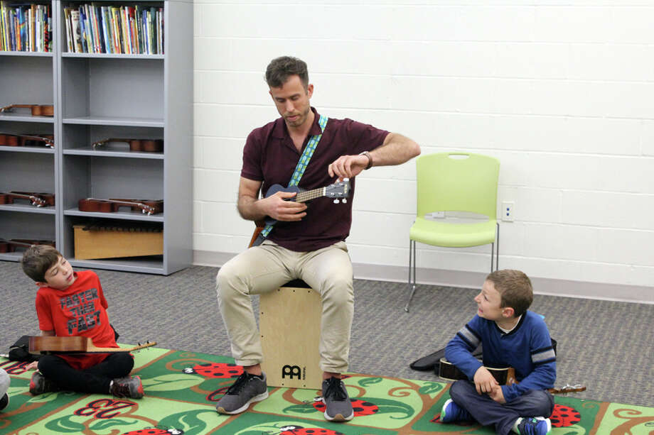 Miller-Driscoll music teacher Chris Johnson tunes a students ukulele. Taken Wednesday May 1 at Miller-Driscoll School. - Lynandro Simmons photo