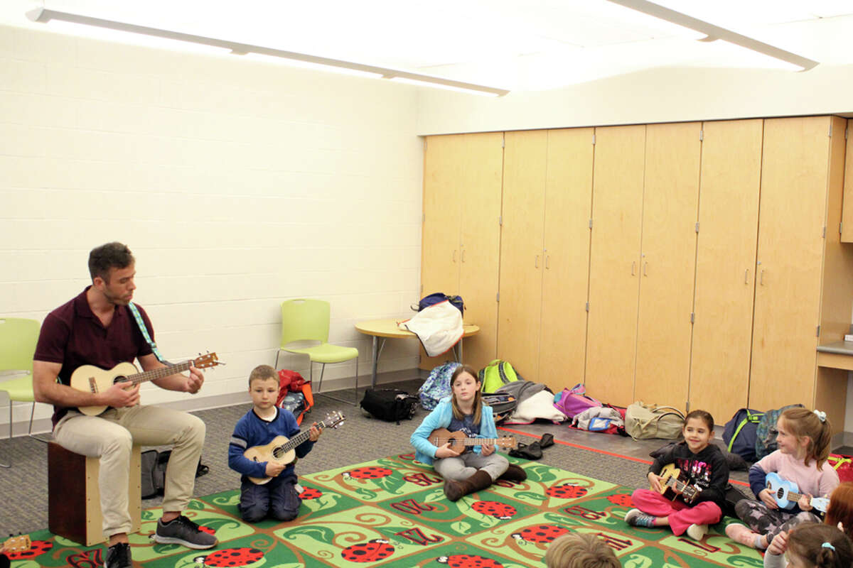 Students follow along as music teacher Chris Johnson leads them in playing the ukulele. Taken Wednesday, May 1 at Miller-Driscoll School. - Lynandro Simmons photo