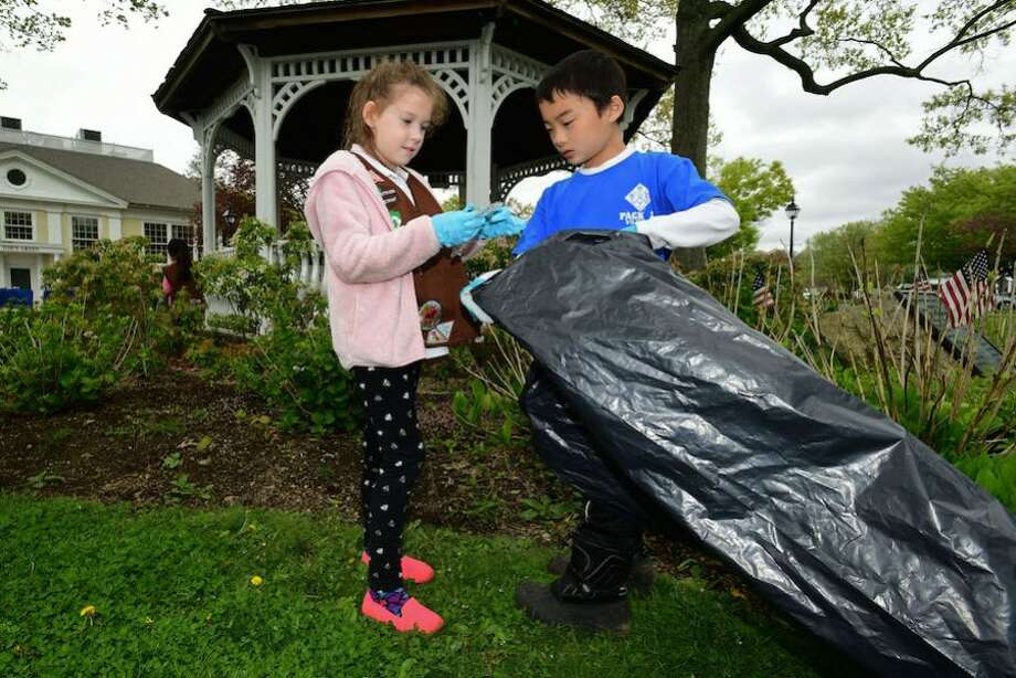 Ruth Frisbee, a Brownie with Wilton Troop 50734, and Alex Shiue, a Cub Scout with Pack 22, participate in the Townwide Cleanup May 4 at the Wilton Town Green.
