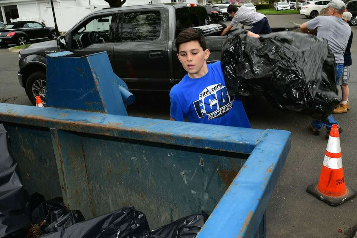 Tood Woodring, 13, heaves a bag of garbage into the Dumpster during the cleanup.