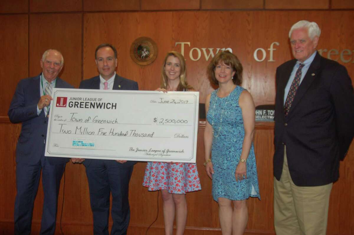 The Junior League of Greenwich presents the final dollars needed to complete its $2.5 million pledge for a public/private partnership with the town to build the town's new municipal pool on Wednesday, June 26, 2019, at Greenwich Town Hall. The pool was opened last year to great success and the league has delivered on its pledge on schedule. From left, Selectman Sandy Litvack, First Selectman Peter Tesei, League President Elizabeth Peyton, President-Elect Hilary Watson and Selectman John Toner are all on hand for the presentation.