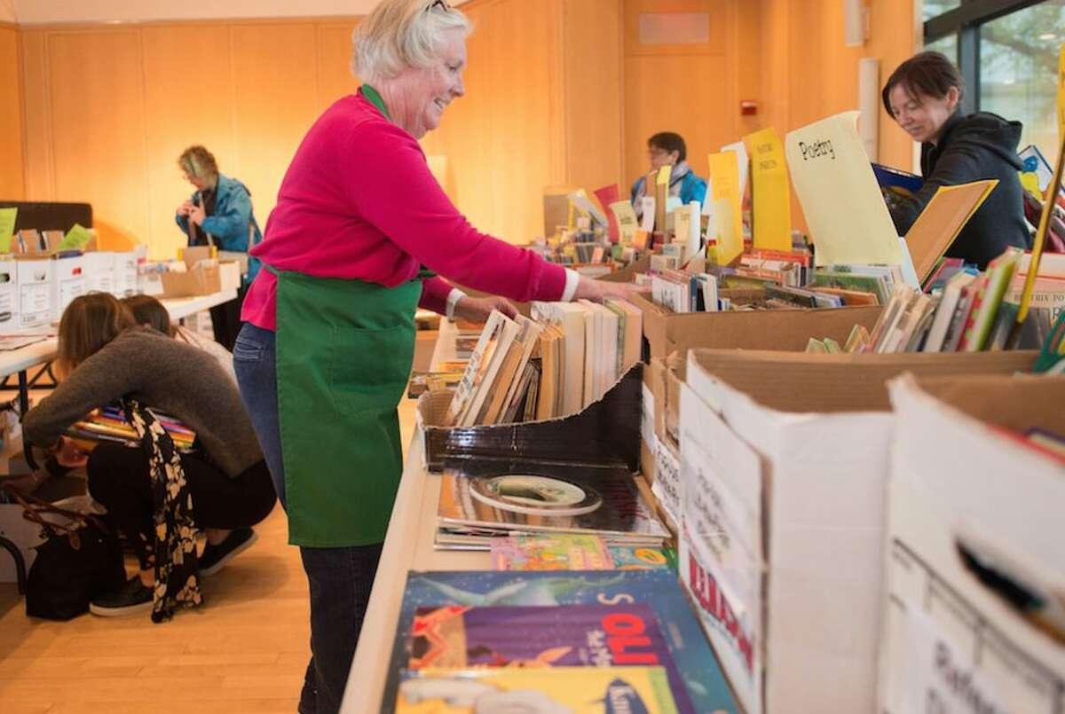 Barbara Quist stocks books at Wilton Library's Gigantic Book Sale .
