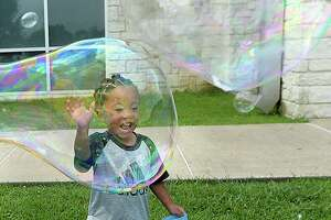Roman Frank reacts as his mother Asia Perkins creates a large bubble during the Texas Energy Museum and Beaumont Public Library's annual Bubble Day event at the Theodore Johns Library Wednesday. A second event will be held July 10, 11:00 a.m. - 12:30 p.m. at the Rogers Park Community Center. Children and adults can enjoy making large bubbles outdoors, and explore the science of bubbles at various hands-on stations inside. Photo taken Wednesday, June 26, 2019 Kim Brent/The Enterprise