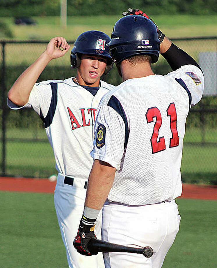 Alton Post 126's Jayce Maag (left) hit a three-run home run Tuesday night in a 12-3 victory over Manchester, Mo. at SIUE. He is shown being greeted is greeted by at home plate after scoring a run in a 2018 District 22 Tournament game.
