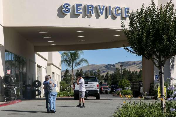 Two men embrace outside the Service Center at the Morgan Hill Ford dealership Wednesday, June 26, 2019, in Morgan Hill, Calif. The night before night police were called to the dealership where a man reportedly killed two people before turning the gun on himself.