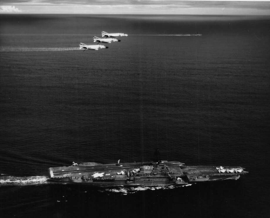 Black and white aerial photograph showing three United States Navy aircraft, McDonnell Douglas F-4 Phantom IIs, in flight over an aircraft carrier ship during the Vietnam War in 1965. Photo: Stuart Lutz/Gado/Getty Images