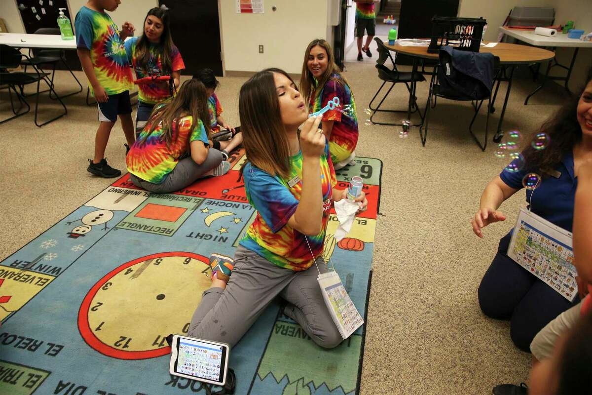 Taryn Morales, speech pathology graduate student, blows bubbles for a child as children with communication disorders learn how to use alternative communication technology at Our Lady of the Lake University on Wednesday, June 26, 2019 during a weeklong summer program called Be AACtive Communicators. OLLU speech pathology students took part in the program as part of their course work and helped 12 kids aged 5 to 17 use tablet-like technology to supplement their communication skills. The free program has been around for three years. (Kin Man Hui/San Antonio Express-News)