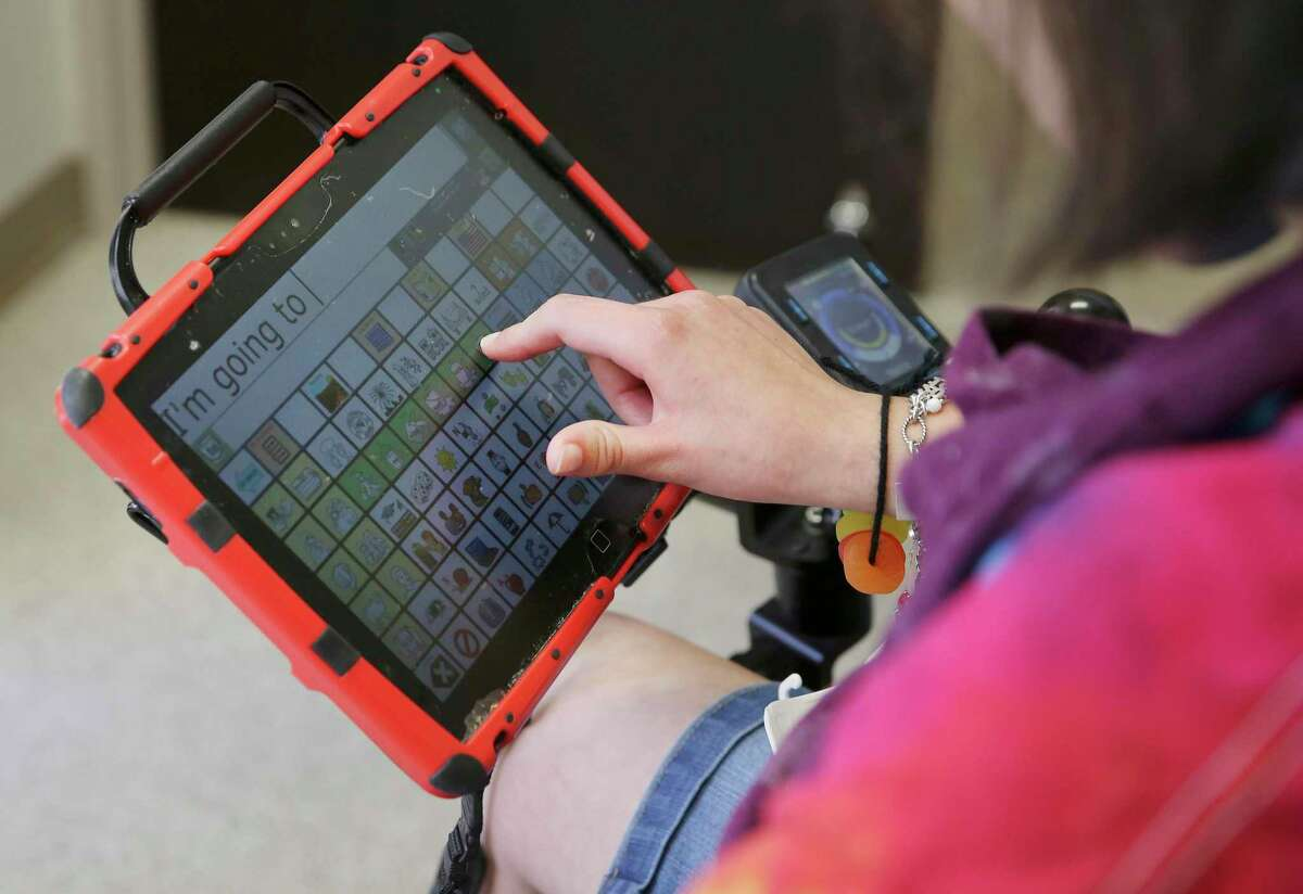 Kayla Janson, 19, types on a device with symbols to convey a message as children with communication disorders learn how to use alternative communication technology at Our Lady of the Lake University on Wednesday, June 26, 2019 during a weeklong summer program called Be AACtive Communicators. Janson has cerebral palsy. OLLU speech pathology students took part in the program as part of their course work and helped 12 kids aged 5 to 17 use tablet-like technology to supplement their communication skills. The free program has been around for three years. (Kin Man Hui/San Antonio Express-News)