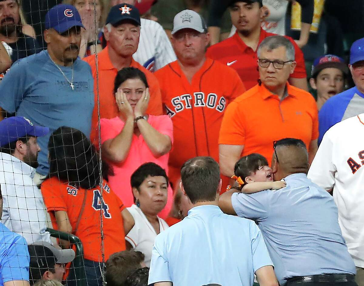 A man carries a small child up the aisle after she was hit by a foul ball of the bat of Chicago Cubs center fielder Albert Almora Jr. during the fourth inning of a major league baseball game against the Houston Astros at Minute Maid Park on Wednesday, May 29, 2019, in Houston.