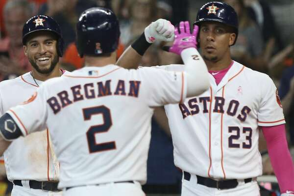 Houston Astros third baseman Alex Bregman (2) celebrates his two-run home run with teammates George Springer and Michael Brantley during the bottom second inning against the Texas Rangers at Minute Maid Park on Sunday, May 12, 2019, in Houston.