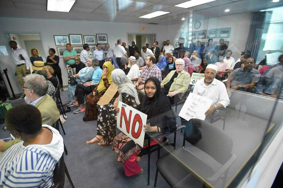 Residents hold signs in silent protest to Stamford Mayor David Martin selection for Chief of Police as nominee Chris Murtha, deputy chief of the Prince George's County Police Department in Maryland, as he faces a line of questions from members of the Board of Representatives' Appointments Committee before hundreds of residents packed in the Legislative Chambers of the Government Center on June 22, 2019 in Stamford, Connecticut. Photo: Matthew Brown / Hearst Connecticut Media / Stamford Advocate