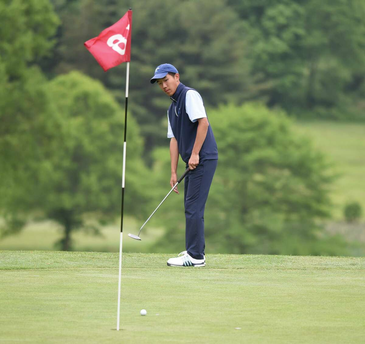 Darien's Alex Gu putts on the 18th green during the FCIAC boys golf championship at Fairchild Wheeler Golf Course in Fairfield on May 30.