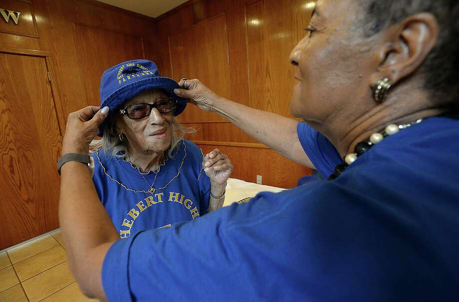 Dorothy Graze Williams, Hebert class of 1934, gets help with her new hat from Willie Shaw, class of 1955, outside the registration room at the MCM Elegante Hotel Wednesday. At 101, Williams will be the oldest alumni attending this year's Hebert High School Mass Reunion, which starts Friday and runs through the weekend.