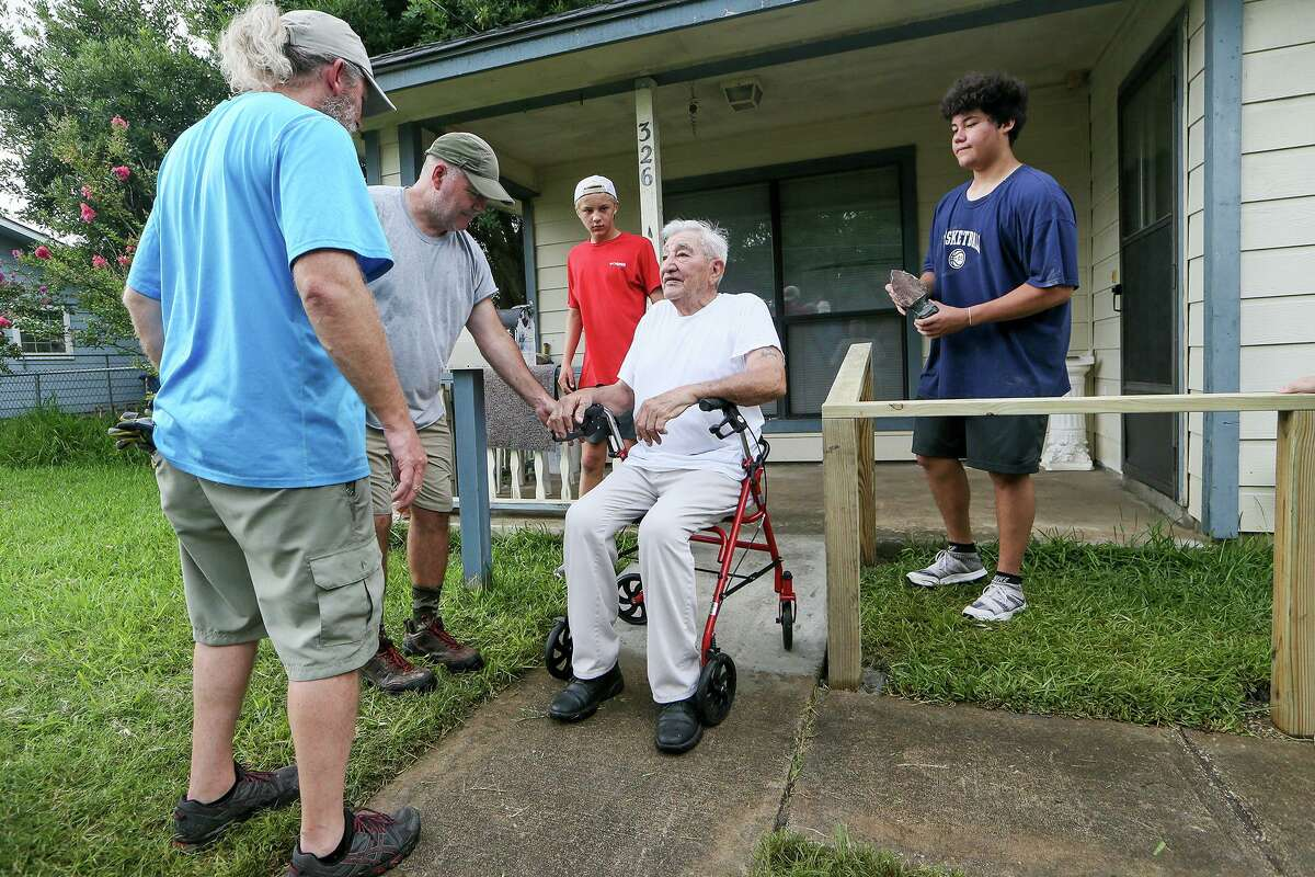 Richard Ramos, seated, checks out an access ramp and handrail that Chris Gordon, from left, Beaman Floyd, Will Hartnett, 16, and Thomas King, 16, built at his home on Albert Street on the West Side as part of a joint Austin-San Antonio church project.