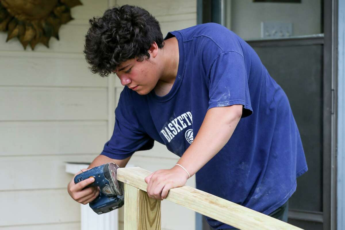 Thomas King, 16, uses a sander to put the finishing touches on a handrail that he and other volunteers from Shepherd of the Hills Presbyterian Church in Austin built at the West Side residence of Richard Ramos on Wednesday, June 26, 2019. Shepherd of the Hills Presbyterian teamed up Devine Redeemer Presbyterian in San Antonio to build the handrail and a ramp and paint the homes of two other elderly families in the neighborhood.