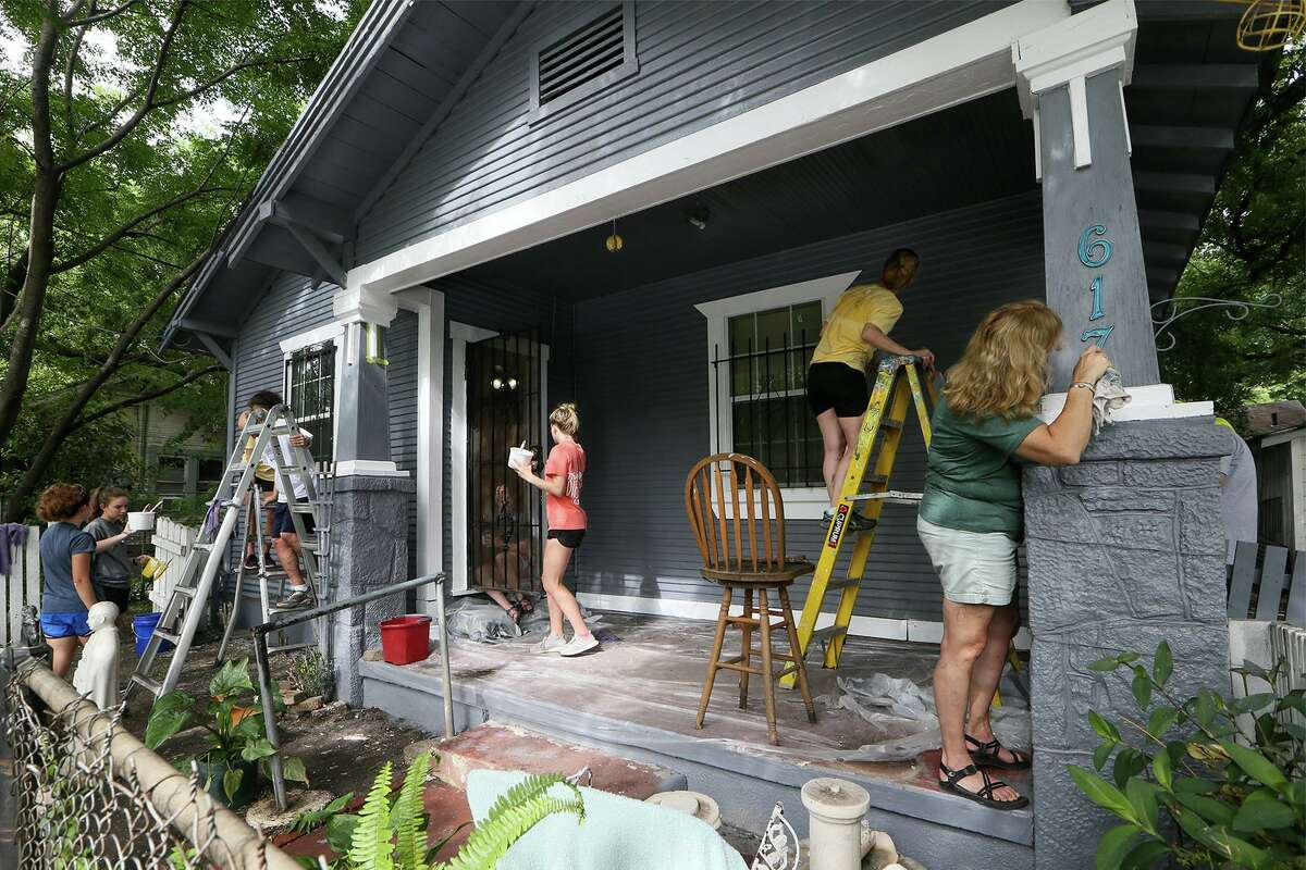 Members of Austin's Shepherd of the Hills Presbyterian Church paint the West Side home of Tirso Romo on Wednesday. ,