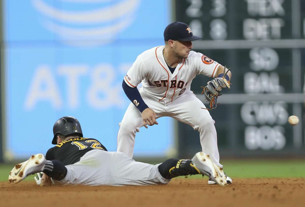 Pittsburgh Pirates left fielder Corey Dickerson (12) slides onto second base as Houston Astros shortstop Alex Bregman (2) is too late to tag him during the top sixth inning of the MLB game at Minute Maid Park on Wednesday, June 26, 2019, in Houston.