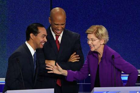 Castro and U.S. Sens. Cory Booker of New Jersey and Elizabeth Warren of Massachusetts share a laugh during break in the debate in Miami.
