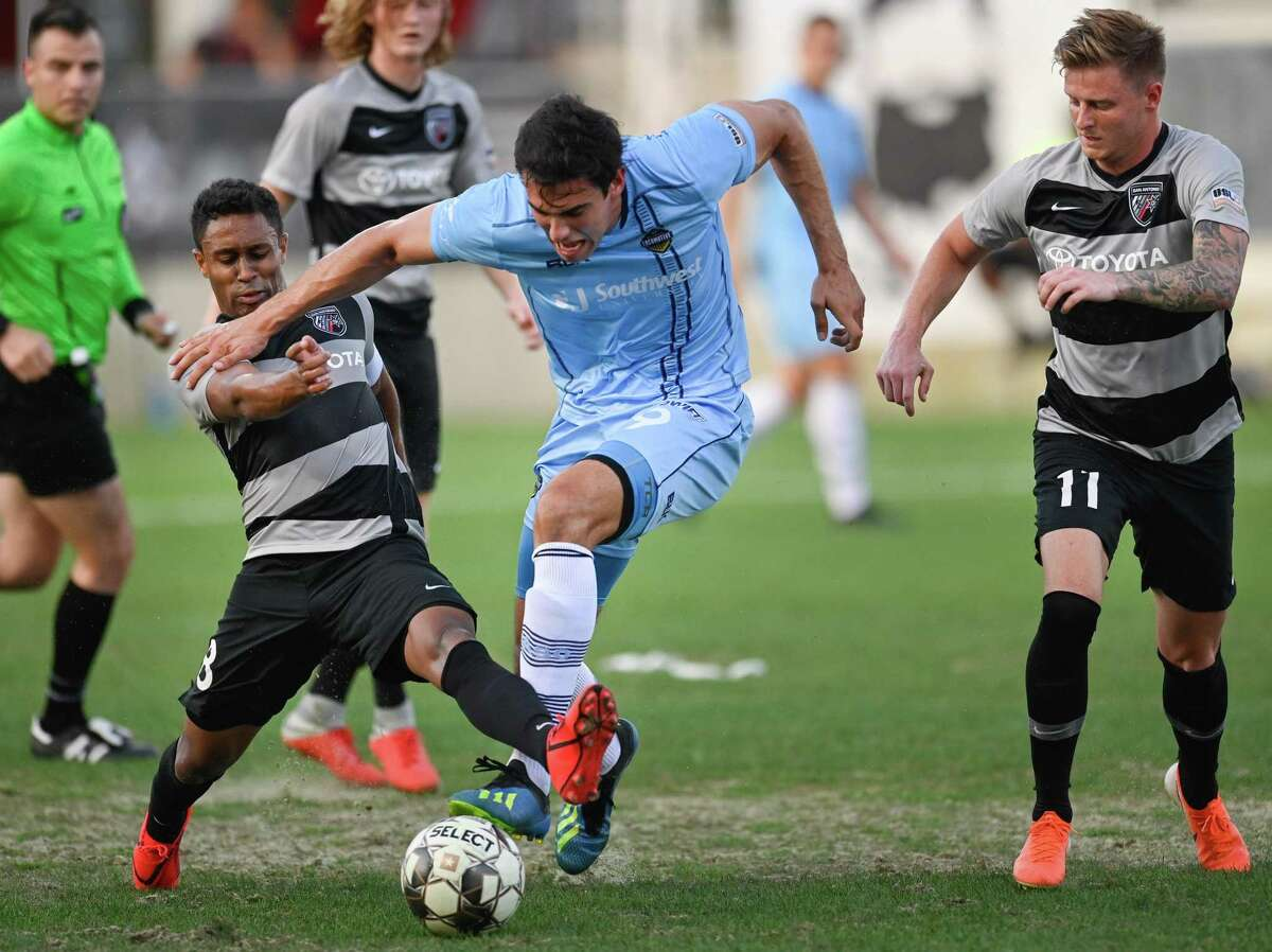 Two San Antonio FC players converge on El Paso Locomotive FC's Omar Salgado as he maintains possession of the ball in a tight spot Wednesday night. San Antonio FC had to play the final 33 minutes - including six of stoppage time - with 10 men because of a red card to Jack Barmby.